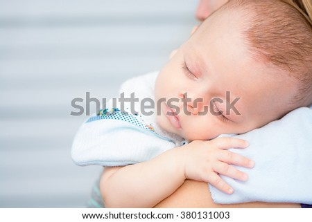 Cute baby sleeping on his mother's shoulder  - stock photo