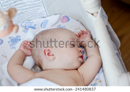 cute baby sleeping sweetly in the cradle at home - stock photo
