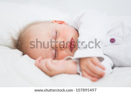 Cute baby sleeping while extending her arms in a room - stock photo