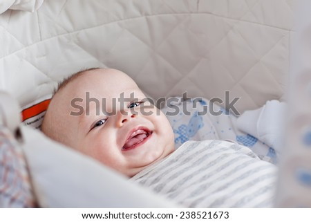 Cute  baby smiling looking at the camera lying in the cradle - stock photo