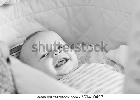 Cute  baby smiling looking at the camera lying in the cradle  ( black and white ) - stock photo
