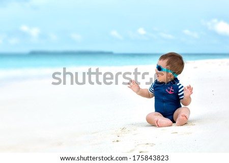 Cute baby smiling, sitting on white sandy tropical beach on Maldives, having vacation. With diving costume or swimwear, sunglasses. - stock photo
