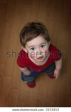 Cute baby standing on her feet, looking up, one hand in pocket. Super cute! - stock photo