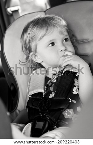 Cute baby sucks his finger sitting in the car seat  ( black and white ) - stock photo