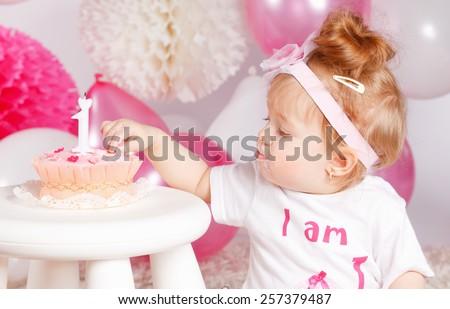 Cute baby tasting the birthday cake - stock photo