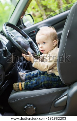 cute baby  toddler boy behind wheel of car - stock photo