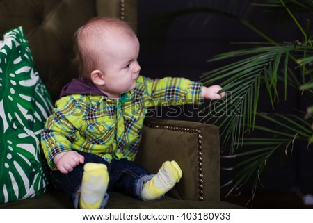 Cute baby toddler sitting on a green armchair near white checkered pillow, fool around - stock photo