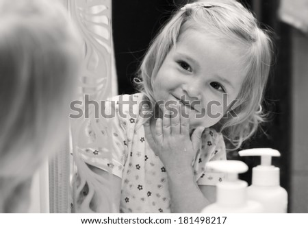 Cute baby washes his face and looks at himself in the mirror ( black and white ) - stock photo