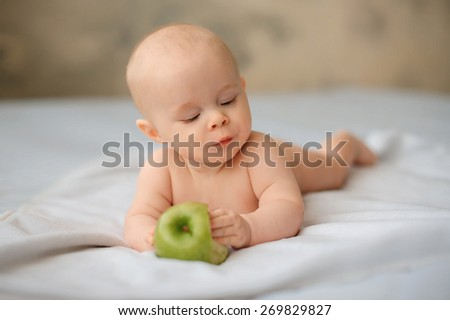 Cute baby with a huge green apple, health, lifestyle - stock photo