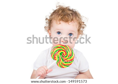 Cute baby with big blue eyes with a colorful candy, isolated on white - stock photo