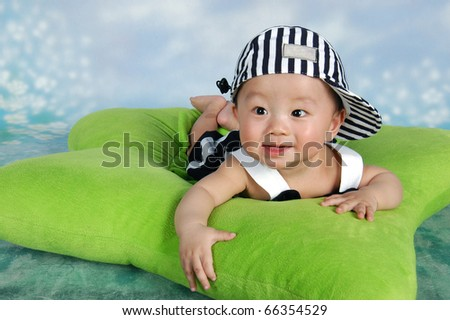 Cute baby with cap lying on a green star-shaped pillow - stock photo