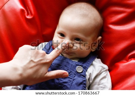 cute baby with finger on the nose - stock photo