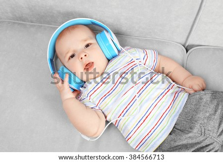 Cute baby with headphones on comfortable sofa in the room, close up - stock photo