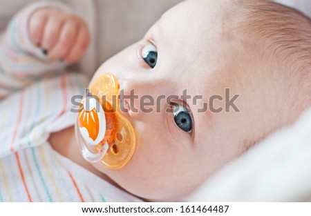 cute baby with pacifier lying in a cradle on a white background - stock photo