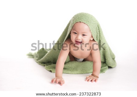 Cute baby with towel. Funny boy covered with green towel - stock photo