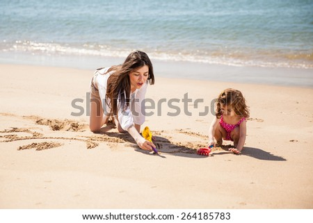 Cute babysitter playing with a little girl and drawing together in the sand at the beach - stock photo
