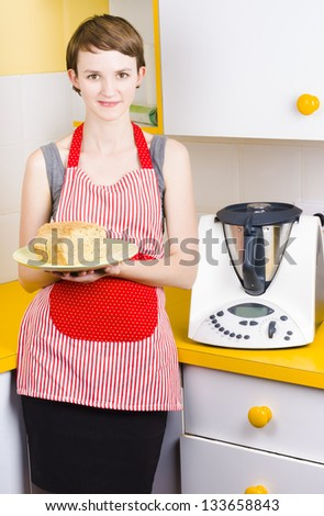 Cute baking woman holding fresh bread with bread making appliance in yellow kitchen - stock photo