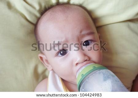 Cute bald baby boy drinking milk from bottle. - stock photo