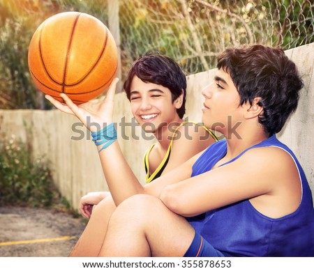 Cute basketball players sitting and resting in timeout, two active teen boys enjoying outdoor games, happy youth lifestyle - stock photo
