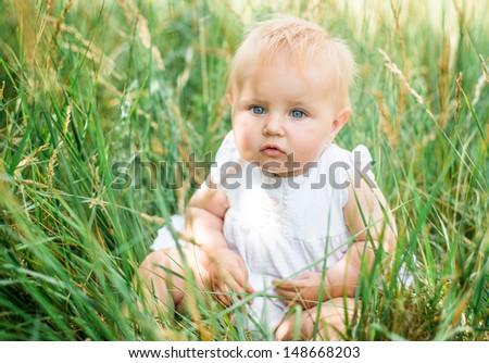 cute beautiful baby in green grass - stock photo