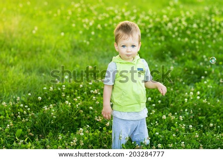 Cute beautiful baby on summer meadow - stock photo