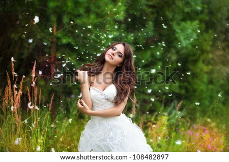 cute beautiful bride in wedding dress in a green grass. - stock photo