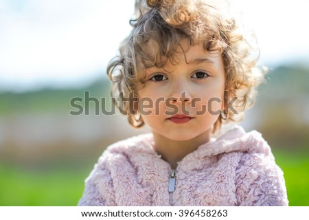 Cute, beautiful curly little girl close-up portrait outdoors. Serious toddler child, kid on a sunny day on the nature at summer or spring. - stock photo