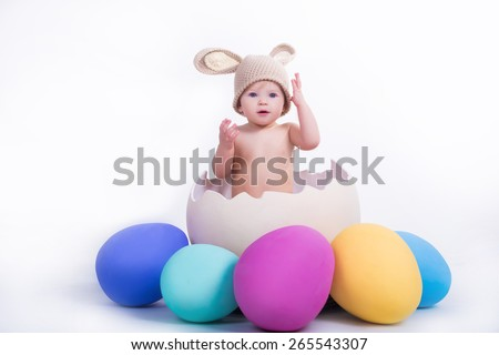 cute beautiful emotional baby with bunny ears sitting in easter egg with colored eggs around on white background - stock photo