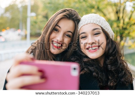 Cute best friends posing for a selfie outdoors in autumn - stock photo