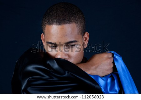 Cute black man with a black cape, looking right over the shiny material - stock photo