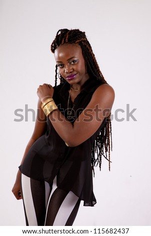 Cute black woman in black and white stripped ants, with her left hand on her right shoulder, and looking into the camera with a serious expression - stock photo