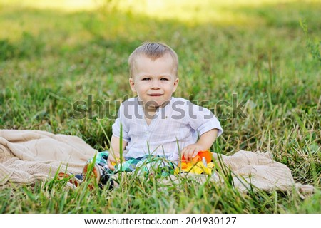 Cute blond baby boy in the plaid shorts playing outdoors in the park with his toy car in the summer day  - stock photo