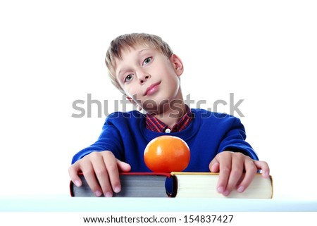 Cute blond boy in a blue sweater sitting with two colorful hardcover books and a tangerine looking bored (isolated on white background)  - stock photo