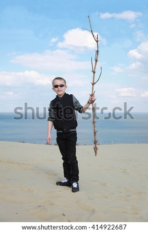 Cute blond boy in sunglasses with a big branch on the seashore - stock photo