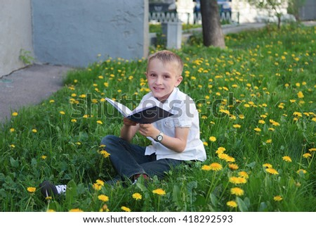 Cute blond boy in white shirt reads book in the field of dandelions - stock photo