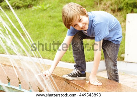cute blond boy playing with a fountain - stock photo