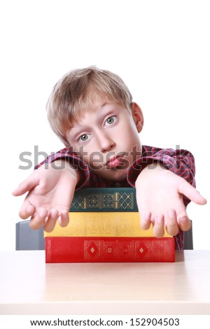 Cute blond boy sitting at a table with a stack of colorful books with a frustrated look   - stock photo