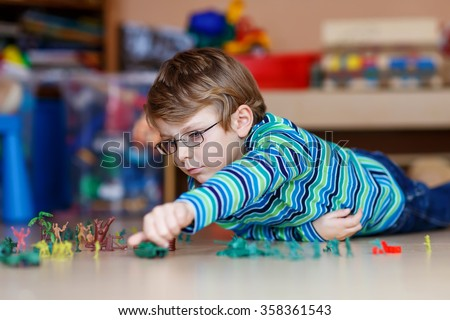 Cute blond child playing with lots of small toy soldiers, indoor. Active kid boy with glasses wearing colorful shirt and having fun at home or at nursery. - stock photo