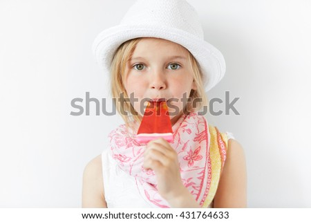 Cute blond girl in summer hat and nice scarf sucking lollipop looking at camera on white background. Tiny kid looks obedient and enjoying her sweet yummy popsicle. - stock photo