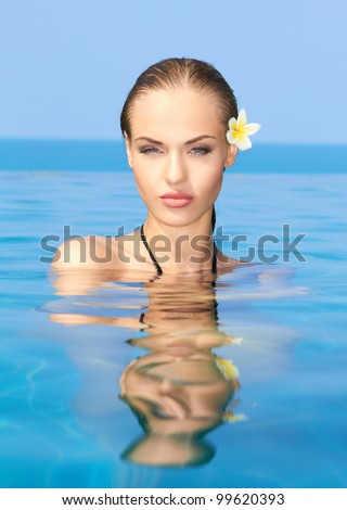 Cute blond girl relaxing in swimming pool - stock photo