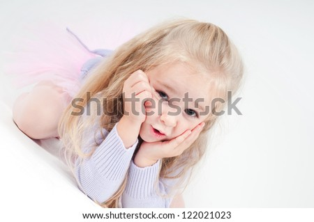 Cute blond girl sitting on the floor - stock photo
