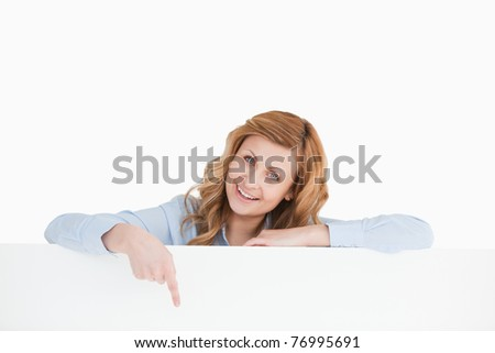 Cute blond-haired woman standing behind an empty white board while showing something - stock photo