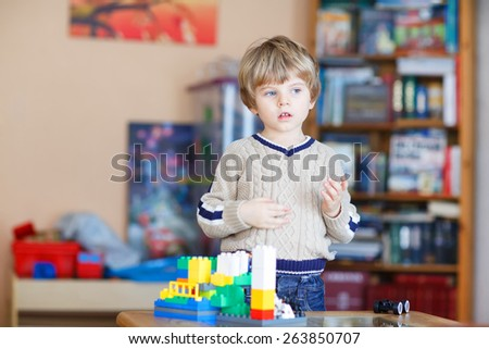 Cute blond kid boy of 3 years playing with lots of colorful plastic blocks indoor. Child having fun with building and creating. - stock photo
