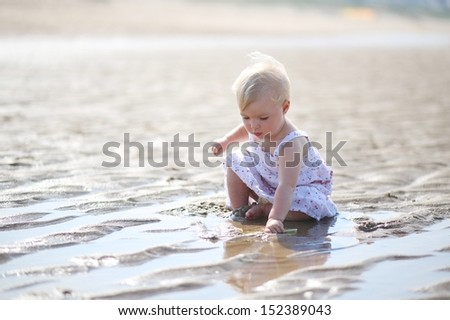 Cute blond little baby girl in beautiful white dress plays with water and sand sitting at s shore of the sea on a long calm empty peaceful beach, sun is shining at her back - stock photo
