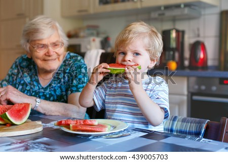 Cute blond toddler boy and his great grandmother eating watermelon in domestic kitchen. Happy family of little kid and retired senior woman enjoying healthy fruit. - stock photo
