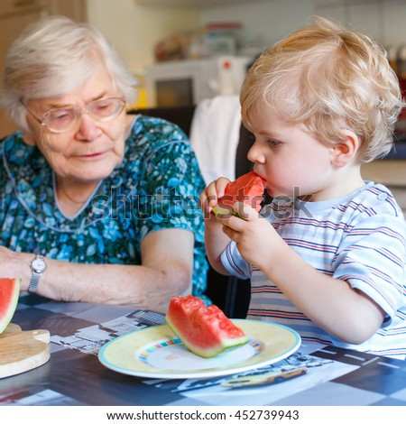 Cute blond toddler boy and his great grandmother eating watermelon in home kitchen. Happy family of little kid and retired senior woman enjoying healthy fruit. - stock photo
