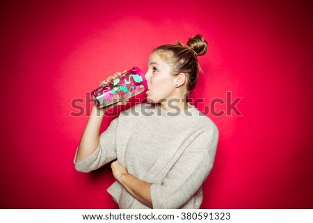 Cute blond woman holding a drinking bottle in studio in front of a strong red background backdrop with contrasty strong vibrant spot light - stock photo