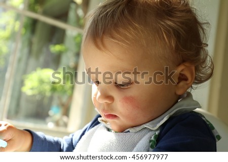 cute blonde baby sitting on a high chair - stock photo