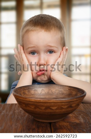 Cute blonde boy naughty and displeased refuses to eat - stock photo
