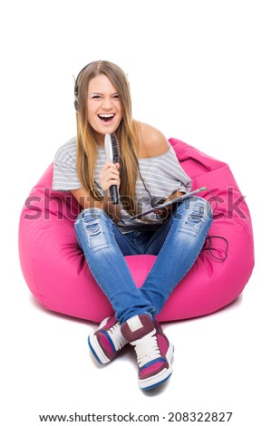 Cute blonde Caucasian teenage girl singing karaoke using hair brush as a microphone holding digital tablet sitting on pink beanbag isolated on white background.  - stock photo